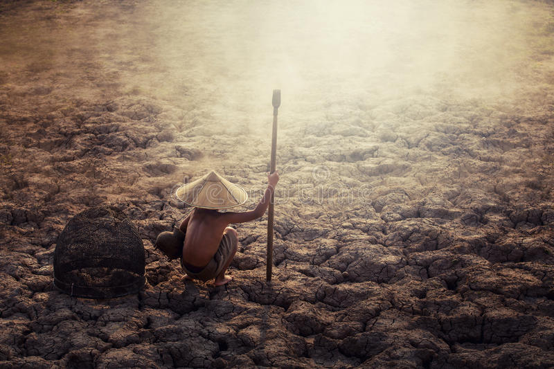 Asian sad a boy sitting on dry ground .concept hope and drought.  stock photography