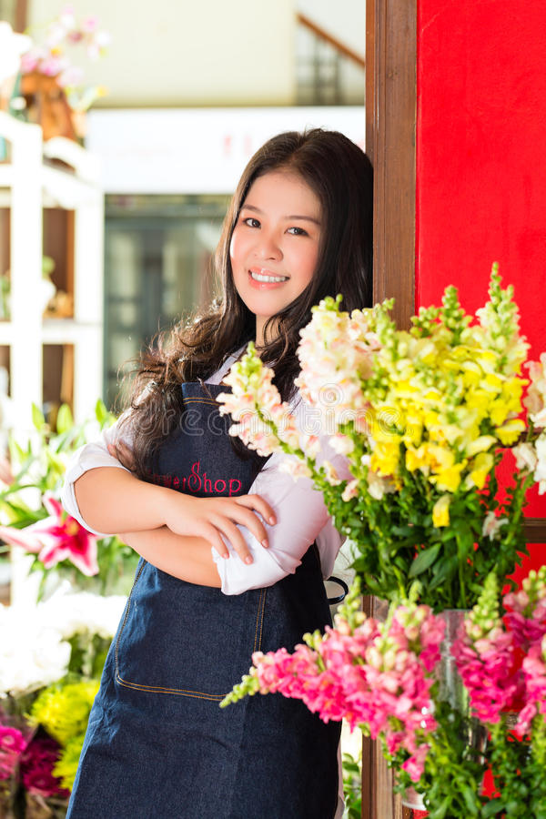 Asian Saleswoman in a flower shop royalty free stock photos