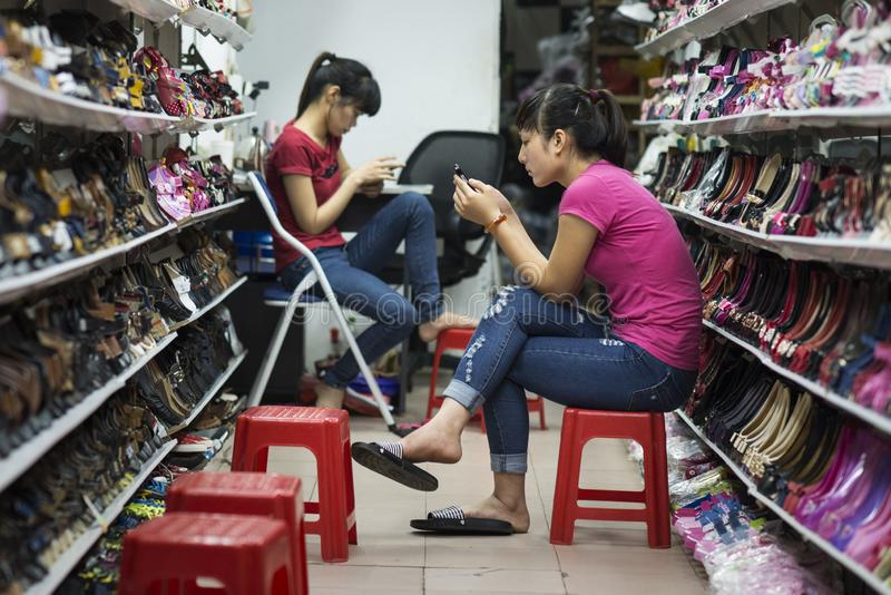 Asian saleswoman in a shoes shop. Shopgirl in a shoes store in Hanoi, Vietnam stock photo