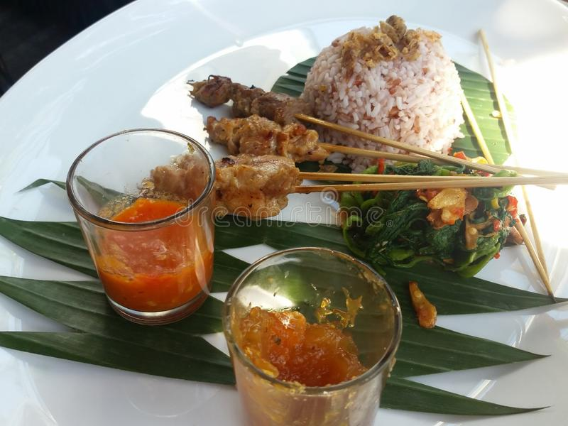 Asian Satay and rice presented beautifully with condiments on a banana leaf. Balinese traditional satay and rice beautifully presented with greens and condiments stock photography