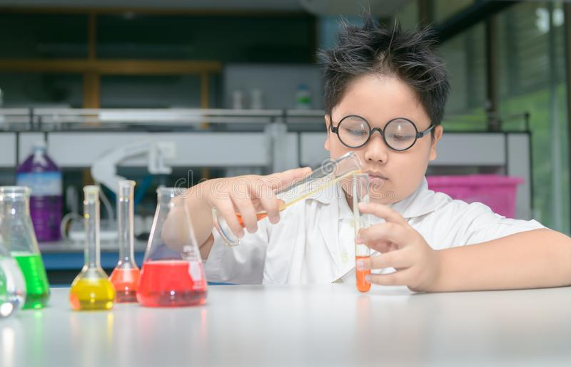 Asian school boy is making science experiments education. Student asian boy is making science experiments education in laboratory school, science and chemical royalty free stock image