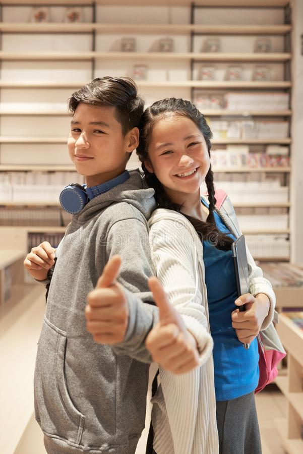 Asian school children giving thumbs up stock images