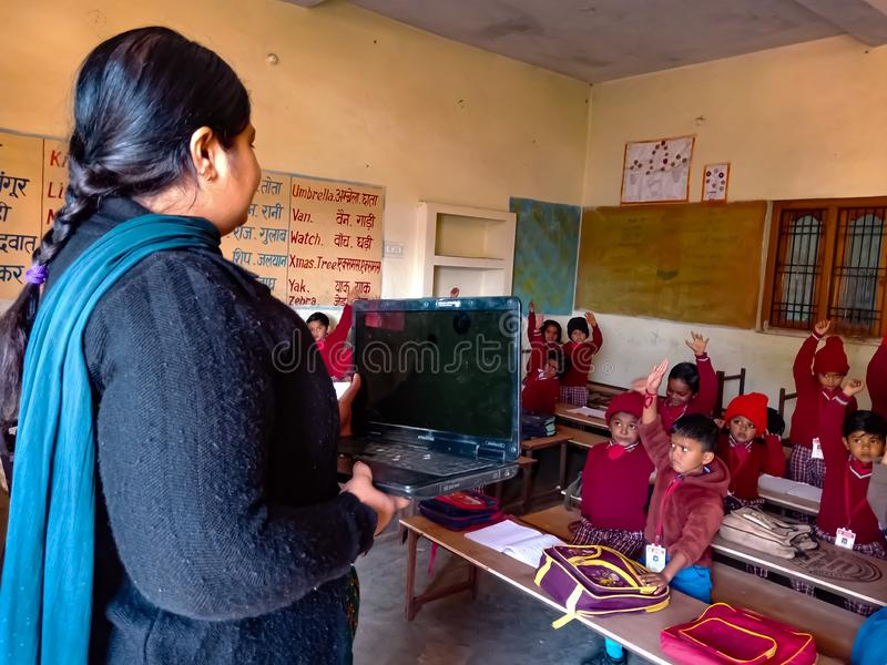 Asian school female teacher giving training about laptop computer system at classroom in india January 2020. Asian school teacher giving training about laptop royalty free stock photos