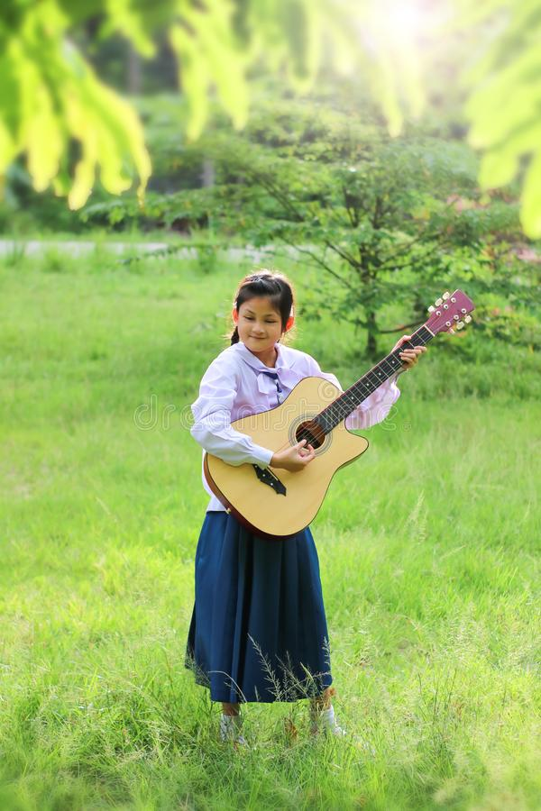 Asian school girl playing the guitar on the lawn , Student learn and practice music instruments stock images