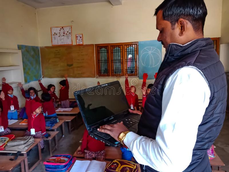 Asian school teacher giving training about laptop computer system at classroom in india January 2020 royalty free stock images