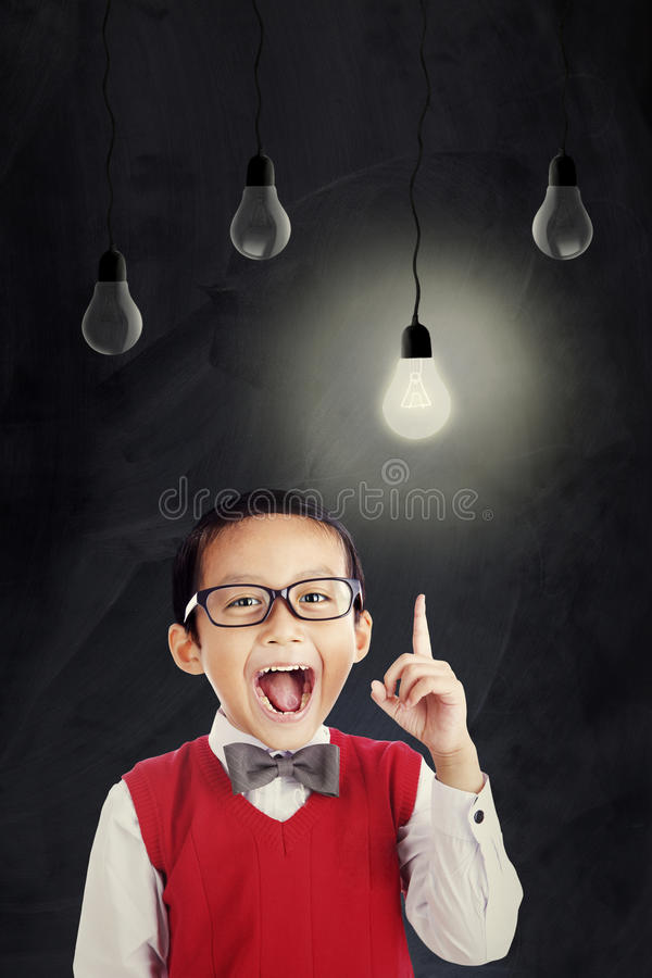 Asian schoolboy with bright lightbulb royalty free stock images