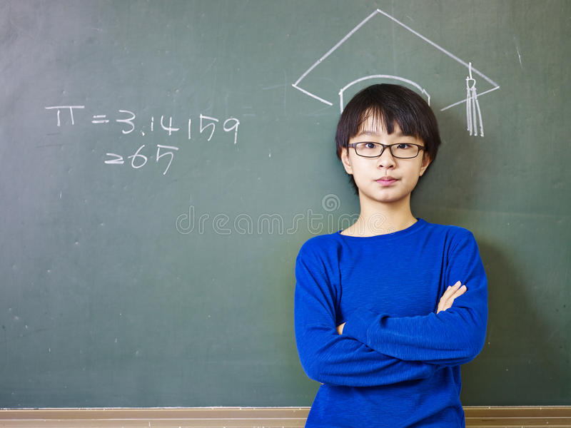 Asian schoolboy standing under a chalk-drawn doctoral cap royalty free stock image