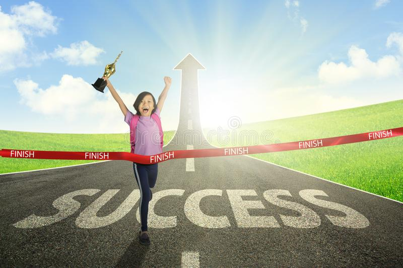 Asian schoolgirl crossing the finish line. Portrait of Asian schoolgirl carrying a trophy while crossing the finish line on the road with success word and upward royalty free stock images