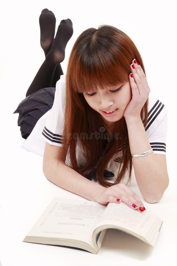Asian schoolgirl reading book stock photography