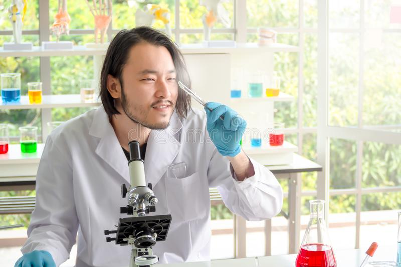 Asian  scientist or chemist  looking at a pill in laboratory, The young man testing medicine in medical experiment. Healthcare,. Pharmaceutical research concept royalty free stock photography