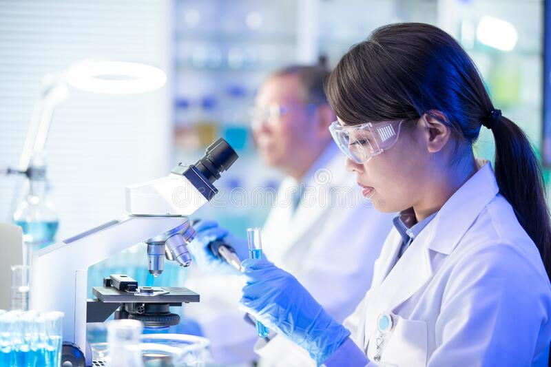 Asian scientist use microscope royalty free stock photography