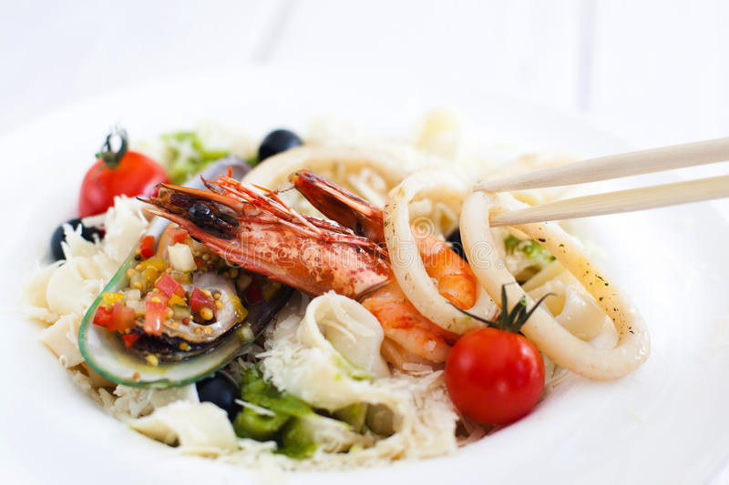 Asian seafood meal, chopsticks using for eating stock image