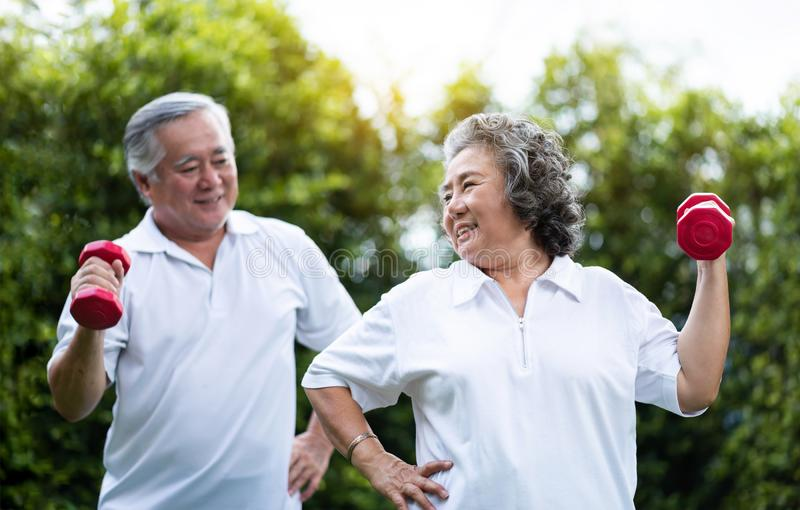 Asian Senior Couple exercising with red dumbbells at the outdoor stock photos