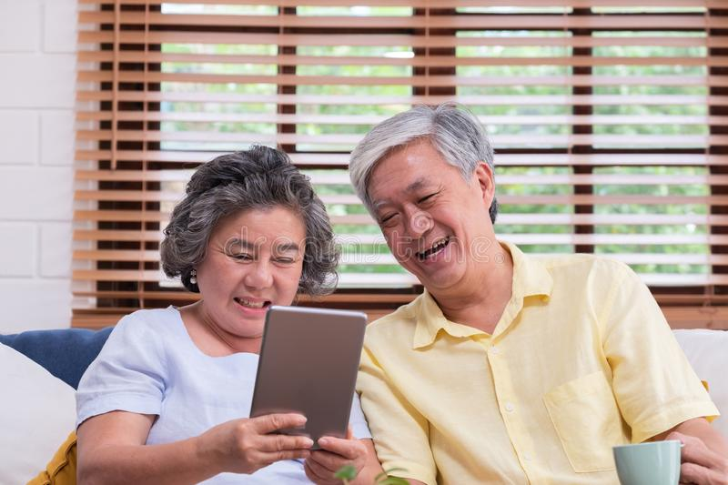 Asian senior couple learn to using table compute on sofa in living room at home.senior with technology lfiestyle.aging at home royalty free stock photo