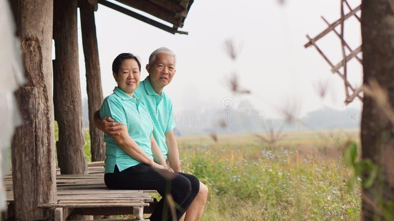 Asian senior couple sitting in the gazebo next to rice field royalty free stock photo