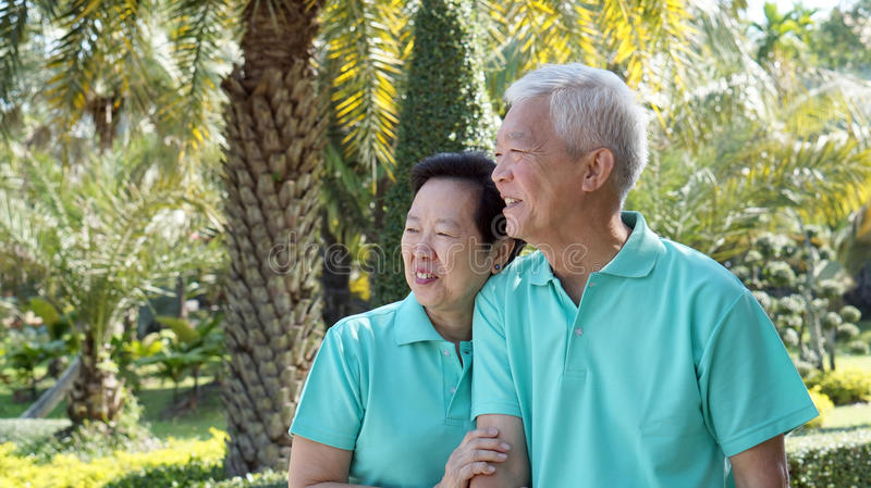 Asian senior couple smiling togher in green nature background stock photography