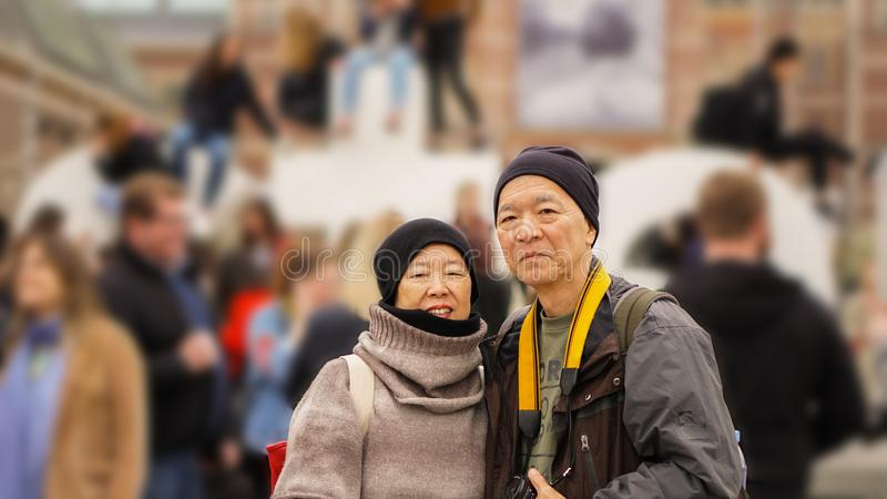 Asian senior couple travel in Europe with tourist crowd at landmark stock photos
