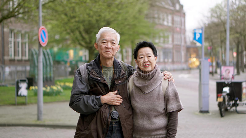 Asian senior couple traveling to Europe together having fun experience together stock image