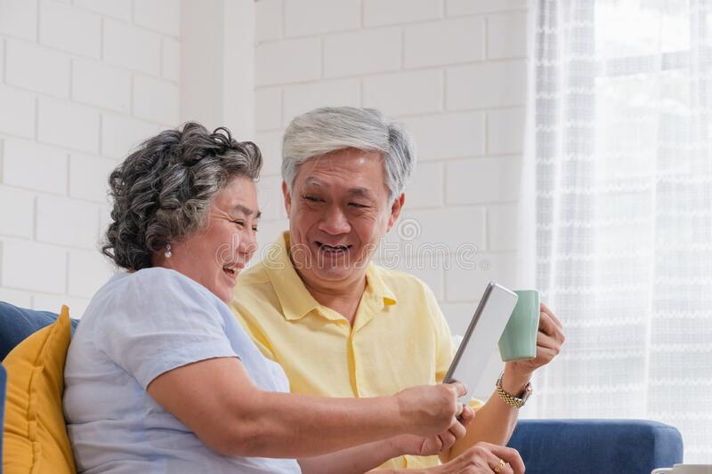Asian senior couple using table compute and drink coffee sitting at sofa in living room at home.senior with technology lfiestyle.a. Ging at home concept royalty free stock photos