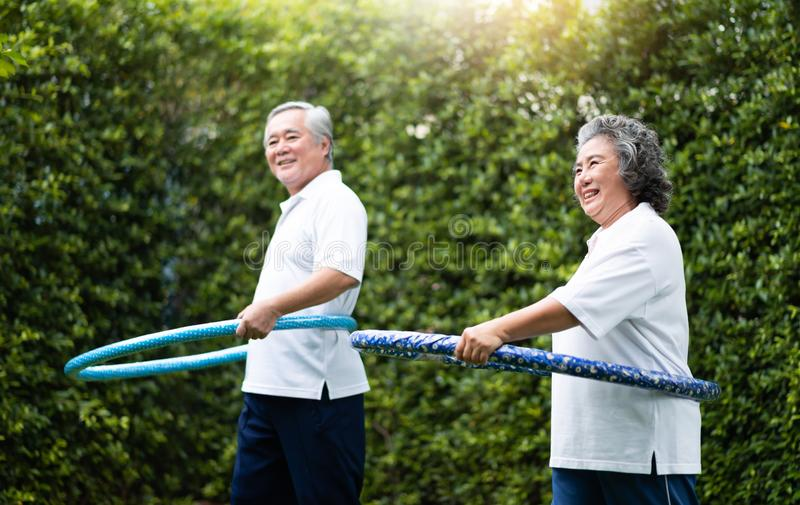 Asian Senior Couple exercising with hula hoops. Asian Senior Couple in white shirt exercising with hula hoops at outdoor park together stock photography
