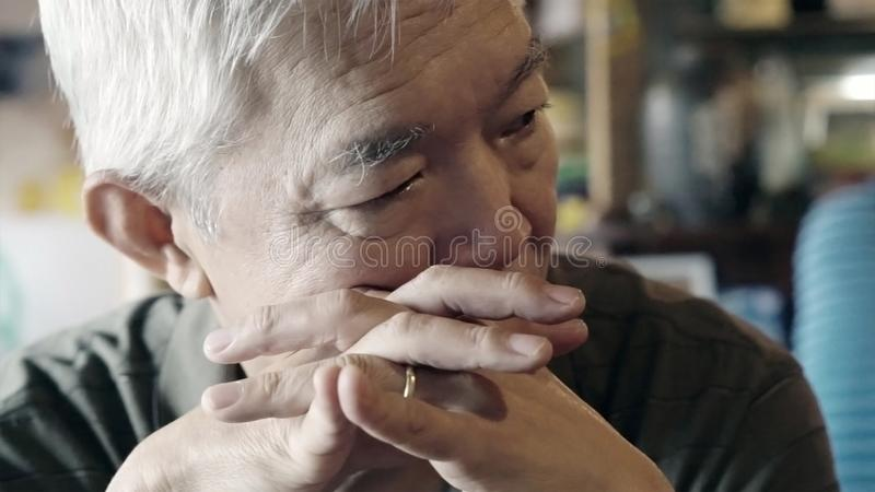 Asian senior elderly man with ring serious thinking and worry ab stock image