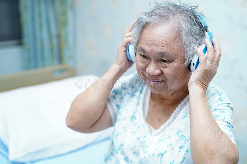 Asian senior or elderly old lady woman patient use earphone while lie down and happy on bed in nursing hospital ward royalty free stock images