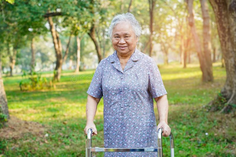 Asian senior or elderly old lady woman patient walk with walker in park. Healthy strong medical concept royalty free stock image
