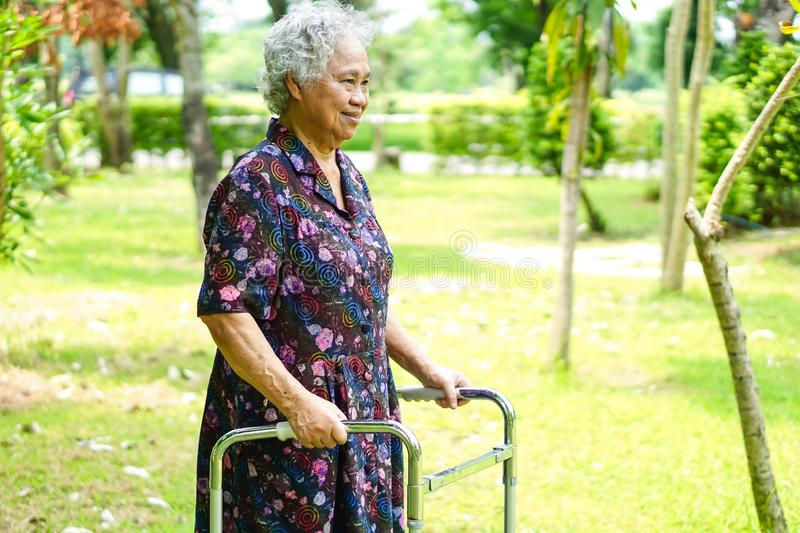 Asian senior or elderly old lady woman patient walk with walker in park : healthy strong medical concept stock photography