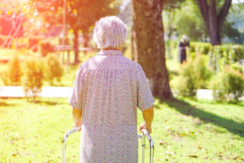 Asian senior or elderly old lady woman use walker with strong health in park. royalty free stock images