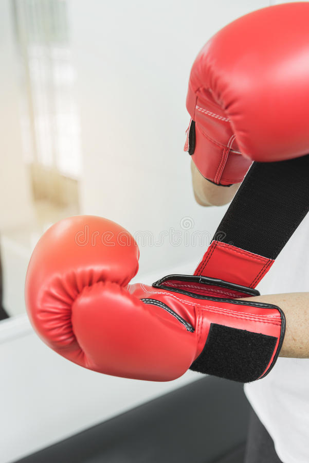 Asian senior fighter man putting his hands into red boxing gloves royalty free stock images