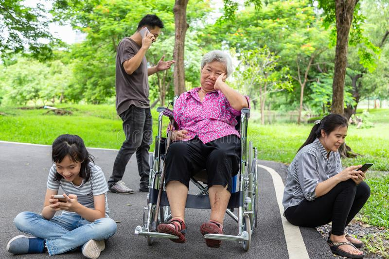Asian senior grandmother is being ignore from family,elderly  bored,sad,frustrated,disregard,parents,child girl with internet, stock images