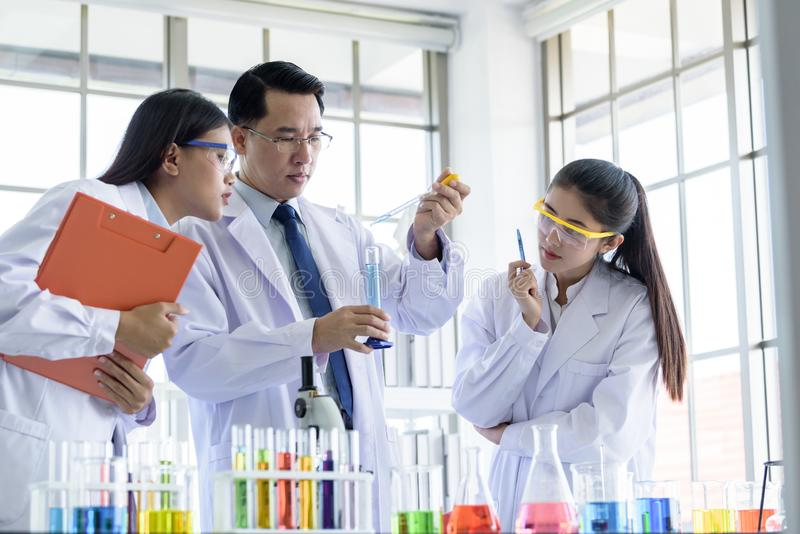 Asian senior laboratory scientist man working at lab with asian young student scientist backgroud stock image