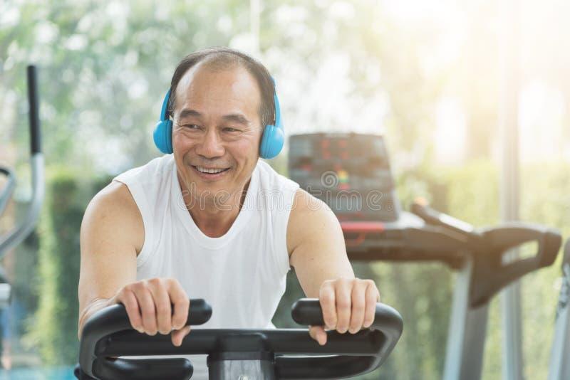 Asian senior man on exercise bike the gym. Copy space royalty free stock photo
