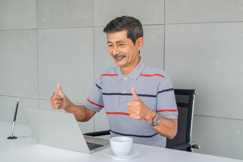 Asian senior man. Glad, lift both thumbs. Sitting look at to laptop computer screen. stock photos