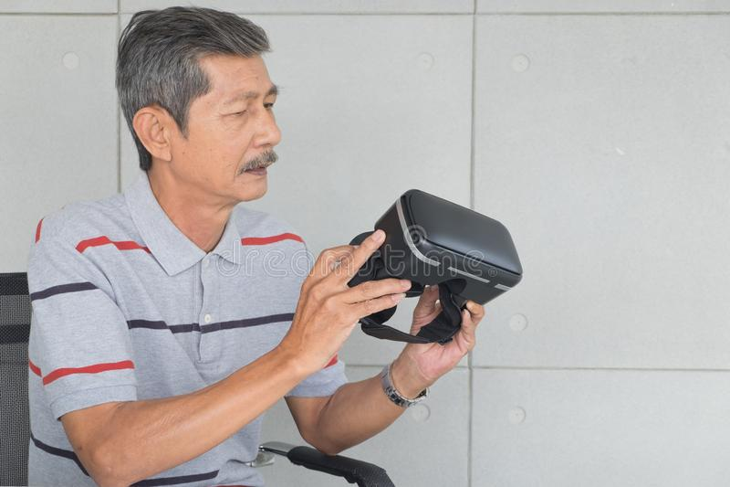Asian senior man. Interested to VR glasses, modern technology. Look at to that and Thinking something royalty free stock image