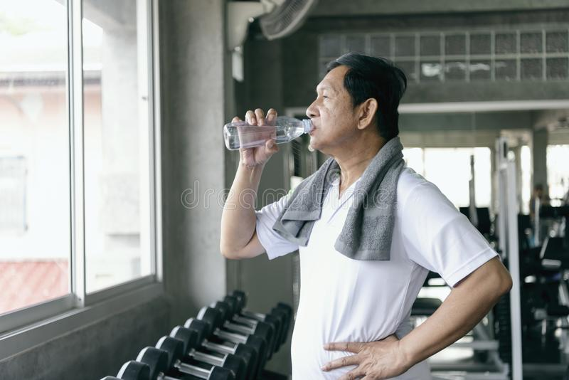 asian senior man thirsty drinking water after exercise in fitness gym. elderly healthy lifestyle. stock photos