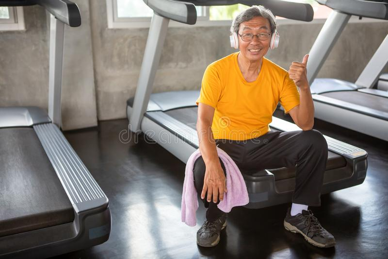 asian Senior man tired taking break after exercise sitting or resting on treadmill and show thumbs up  in fitness gym . walking royalty free stock photos