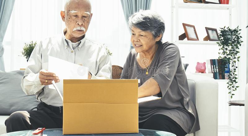 Asian senior man and woman open box with smile face. Delivery, mail, shipping and people concept - senior men and women opening parcel box at home royalty free stock photography