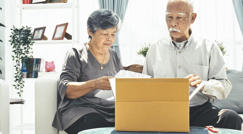 Asian senior man and woman open box with smile face. Delivery, mail, shipping and people concept - senior men and women opening parcel box at home stock photo