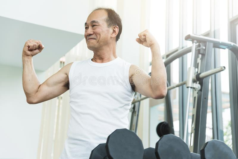 Asian senior man working out at the gym. stock photo