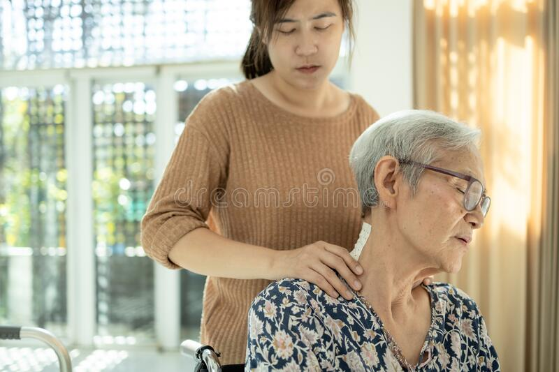 Asian senior mother have nerve pain,shoulder ache,neck pains,female caregiver or daughter massaging her shoulders, frustrated stock photo