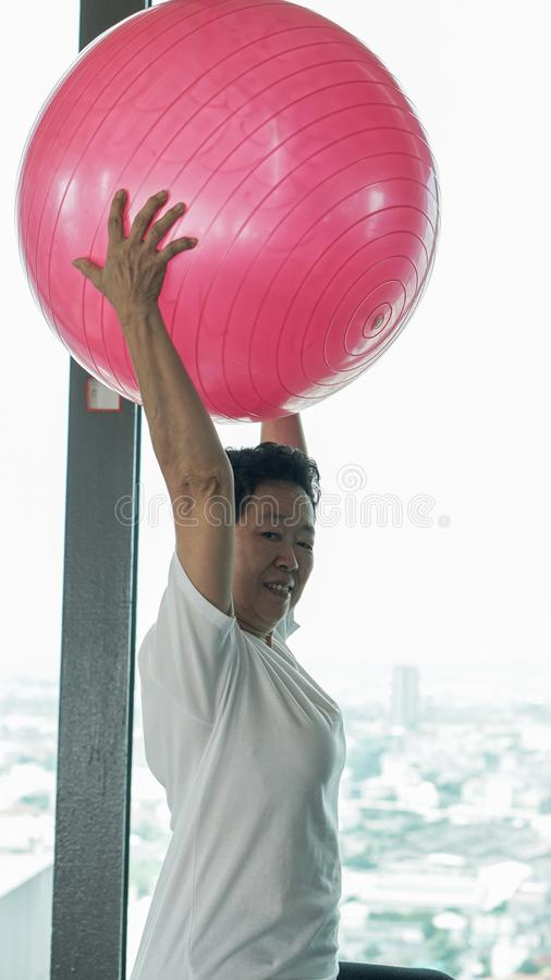 Asian senior old healthy woman exercise with pink gymnastic ball royalty free stock image