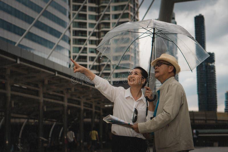 Asian senior traveler couple with map and umbrella having city tour during rainy season stock image