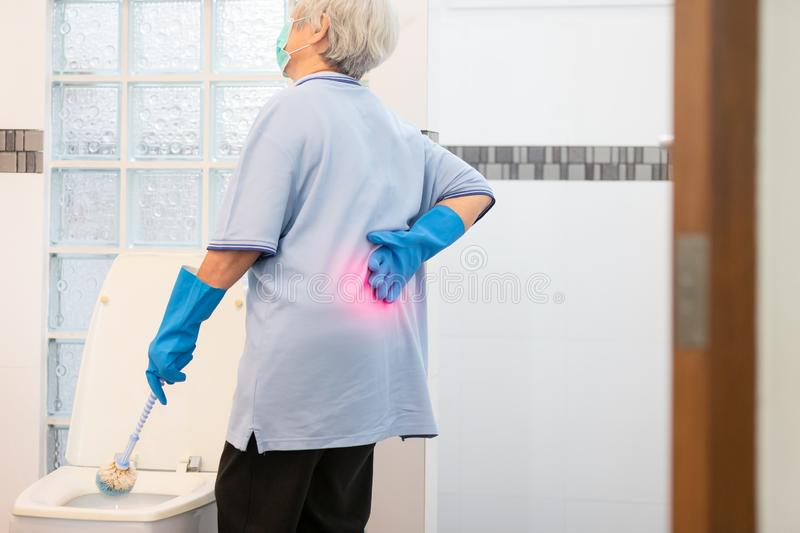 Asian senior woman in blue glove,cleaning toilet bowl,female elderly housekeeper hands touching back pain having backache,muscle, stock image