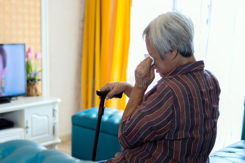 Asian senior woman is crying,hold a tissue paper in hand and wiping in her eyes form watching movies dramas series on TV,elderly royalty free stock images