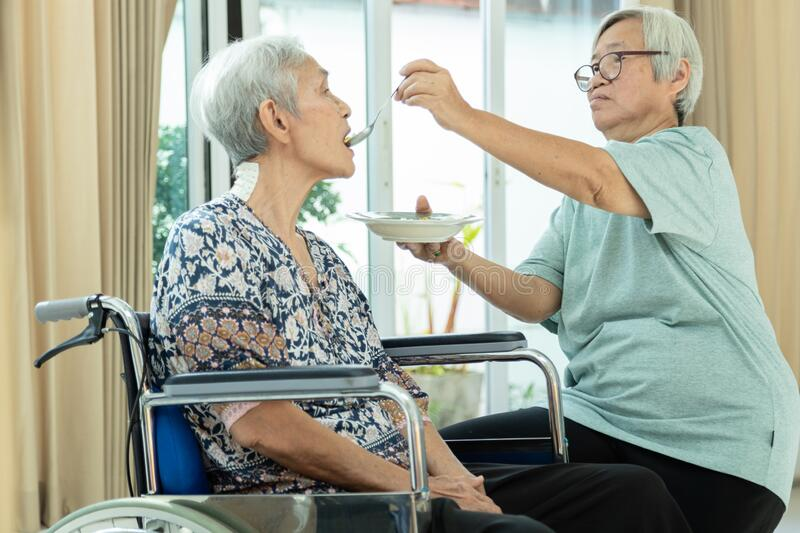 Asian senior woman is feeding older sister with thai food,female elderly helping her to eat and take a drug, love,care and concern. Asian senior women is feeding royalty free stock photography