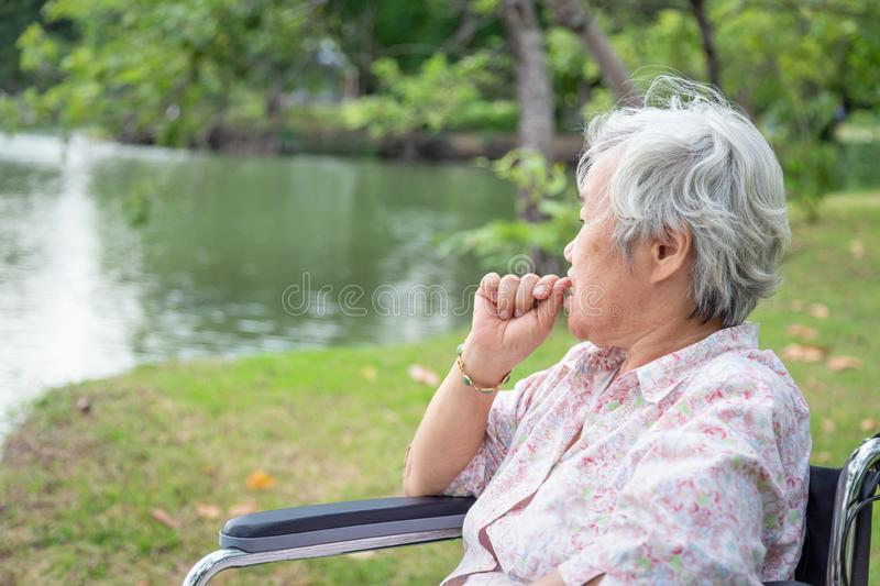 Asian senior woman feeling stressed,worried female bites finger nails in wheelchair outdoor park,elderly people with nervous stock photos