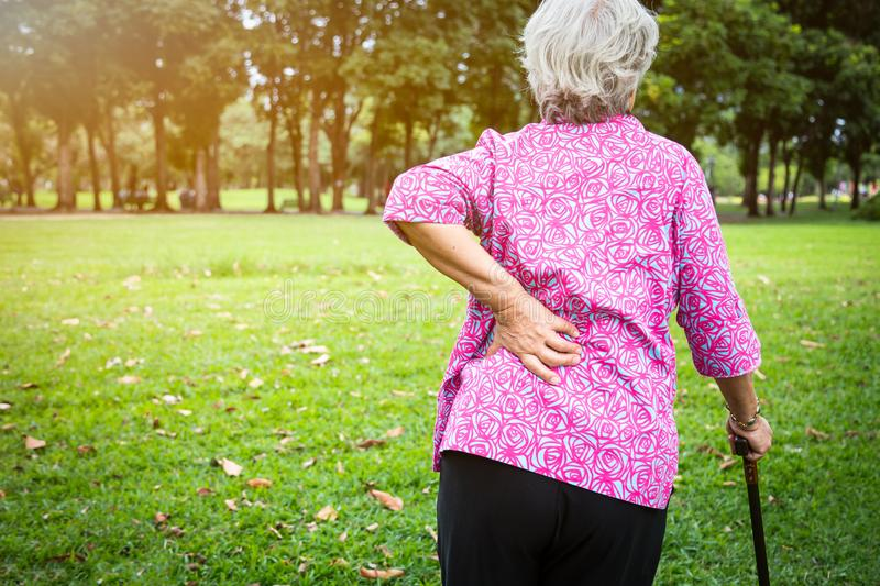 Asian senior woman hands touching back pain while walking in nature in summer,female patient having backache,muscle,hip pain in royalty free stock image