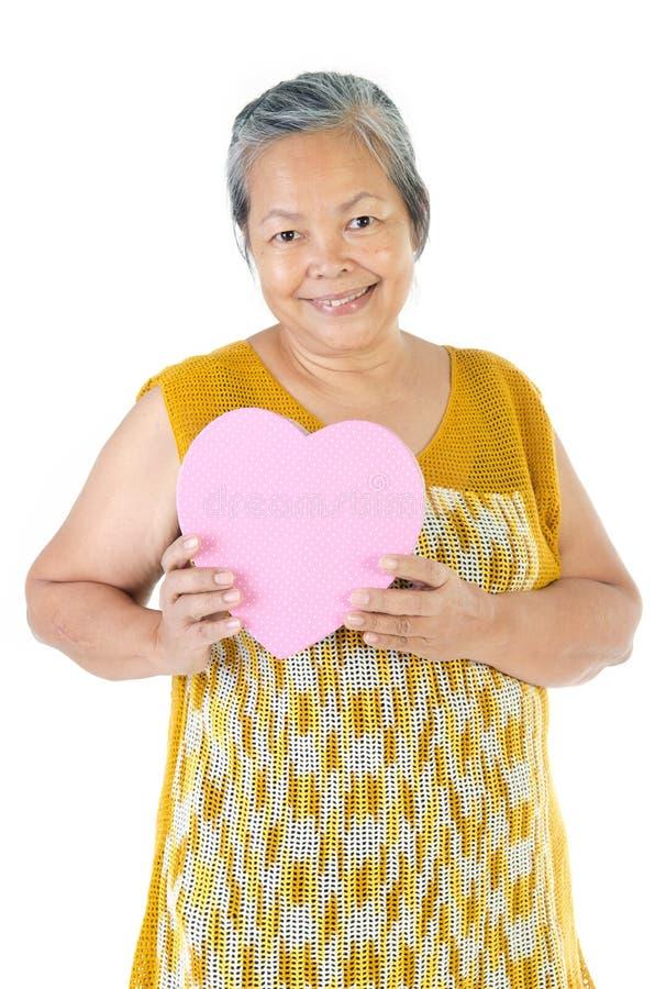 Asian Senior woman holding a gift box. Asian Senior woman holding a heart gift box stock photos