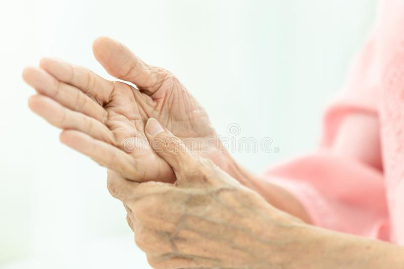 Asian senior woman is massaging her own hand,Elderly woman suffering from pain in hand,arthritis,beriberi stock image